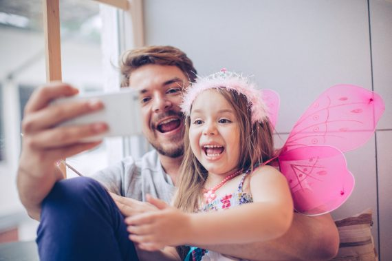 Father and daughter enjoying at home. Little girl wearing fairy costume and tiara. Sitting on window wooden seat. Taking selfies with smart phone.