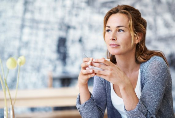 Woman sitting in coffee shop holding her coffee looking contemplative with copyspace