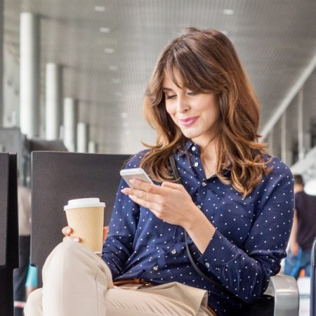 Young woman waiting for flight at the airport lounge. Businesswoman sitting on a bench with coffee and using a mobile phone.